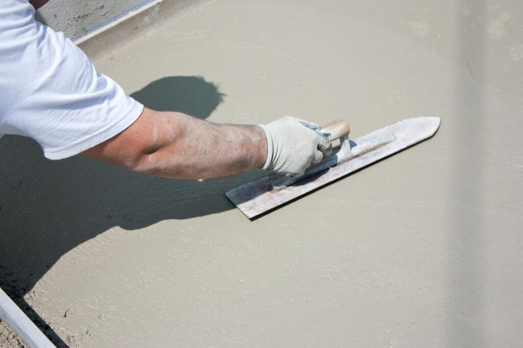 man flattening the concrete cement