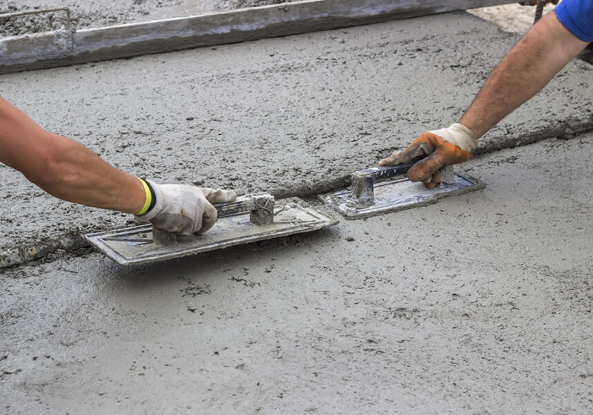 men flattening the concrete cement on the floor